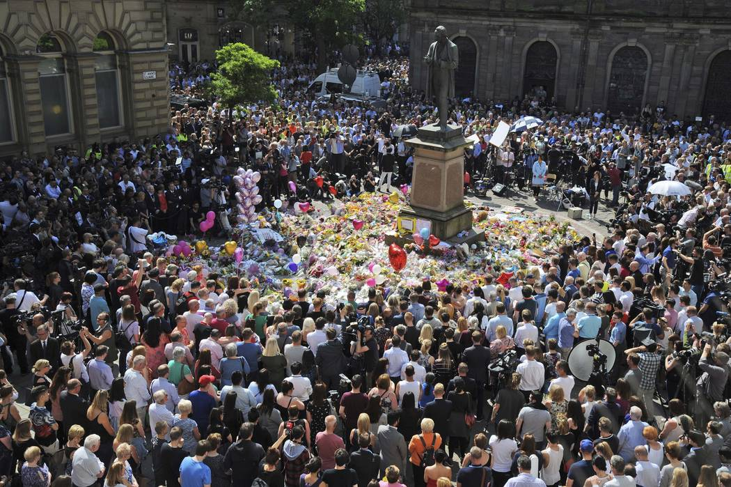 People attend a one minute silence to the victims of Monday's explosion at St Ann's Square in Manchester, England Thursday May 25 2017.  More than 20 people were killed in an explosion following a ...