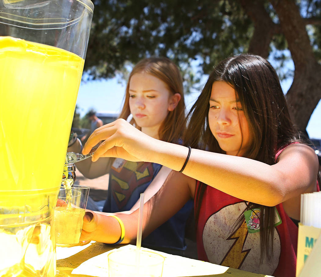 Mallory Poushay, 13, left, and Alyciana Rivas, 13, hand out lemonade during a fundraiser for Alex's Lemonade Stand Foundation, a national childhood cancer foundation, at Sunset Park in Las Vegas,  ...