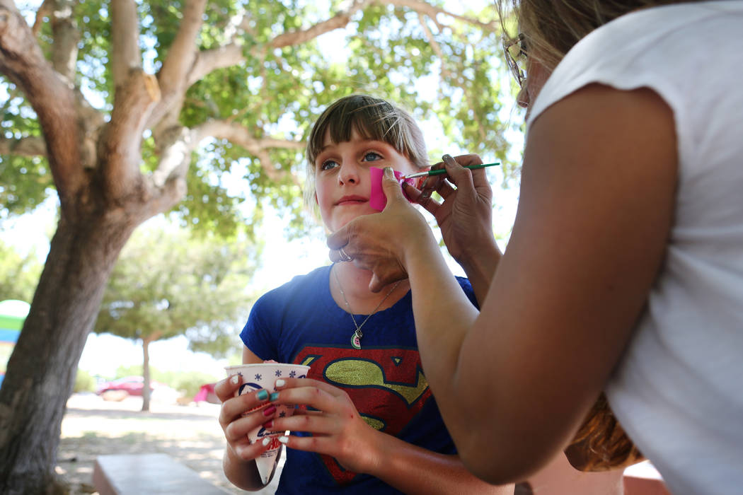 Katelyn Chicarelli, holds her shaved ice and gets her face painted during a fundraiser for Alex's Lemonade Stand Foundation, a national childhood cancer foundation, at Sunset Park in Las Vegas, Su ...