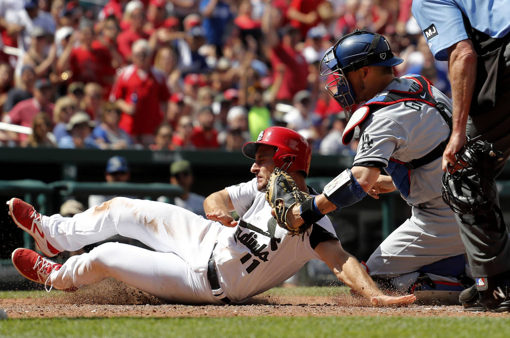 St. Louis Cardinals' Paul DeJong, left, is tagged out at home by Los Angeles Dodgers catcher Yasmani Grandal during the seventh inning of a baseball game Monday, May 29, 2017, in St. Louis. (AP Ph ...