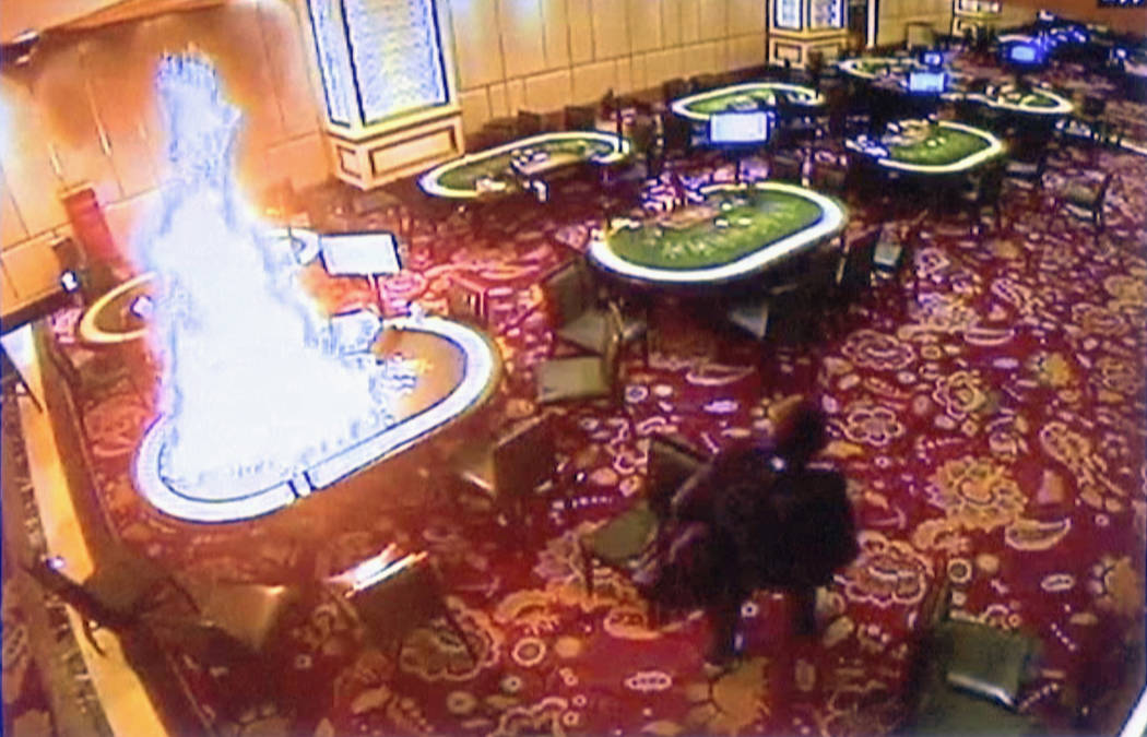 In this image made from security video released by Manila Police and Resorts World Manila on Saturday, June 3, 2017, a gunman walks away after setting fire to a gambling table in the Resorts World ...