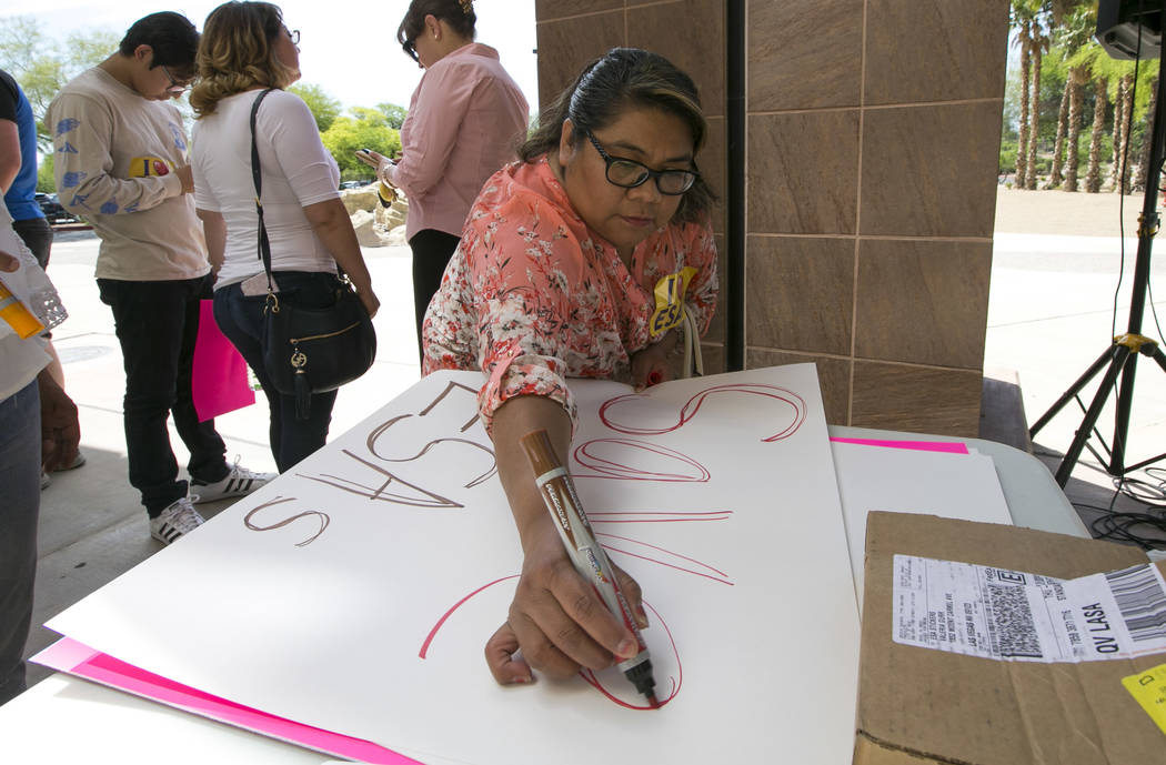 A woman makes a signs before the start of a rally supporting a measure for the Nevada Education Savings Account outside of the Grant Sawyer Building in Las Vegas on Saturday, June 3, 2017. Richard ...