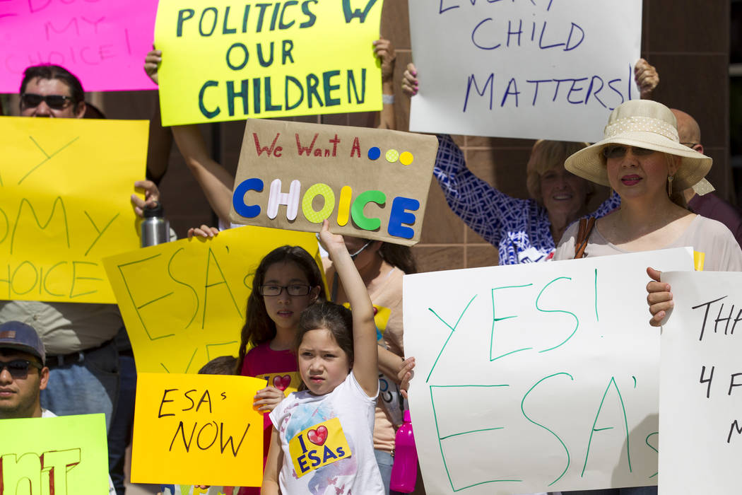 Eight-year-old Estela Manzano, center, joins her parents during a rally supporting a measure for the Nevada Education Savings Account outside of the Grant Sawyer Building in Las Vegas on Saturday, ...