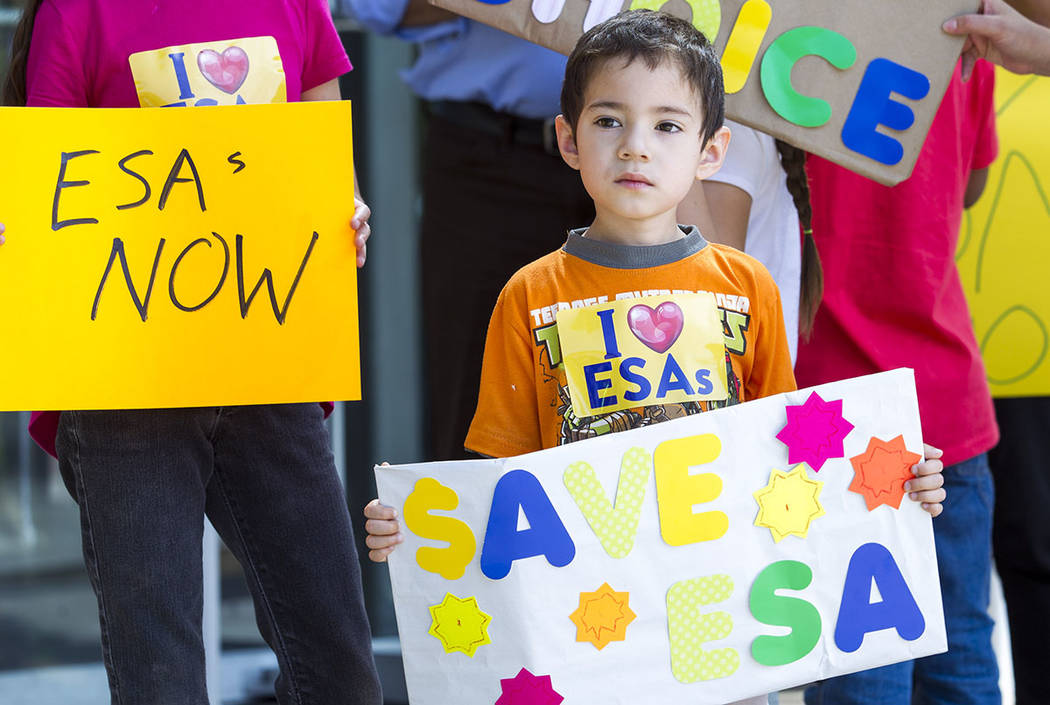 Five-year-old Casir Manzano joins his parents during a rally supporting a measure for the Nevada Education Savings Account outside of the Grant Sawyer Building in Las Vegas on Saturday, June 3, 20 ...