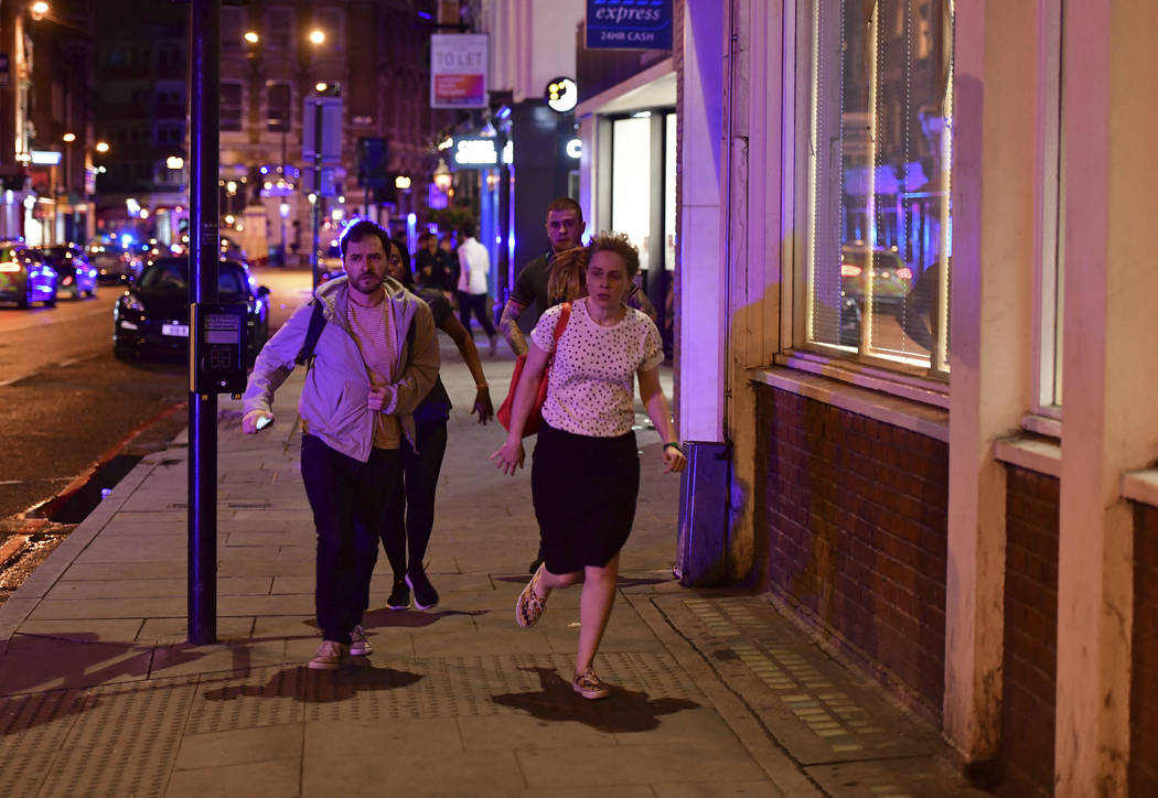 """People run down Borough High Street as police are dealing with a """"major incident"""" at London Bridge in London, Saturday, June 3, 2017.  London incident. (Dominic Lipinski/PA via AP)"""