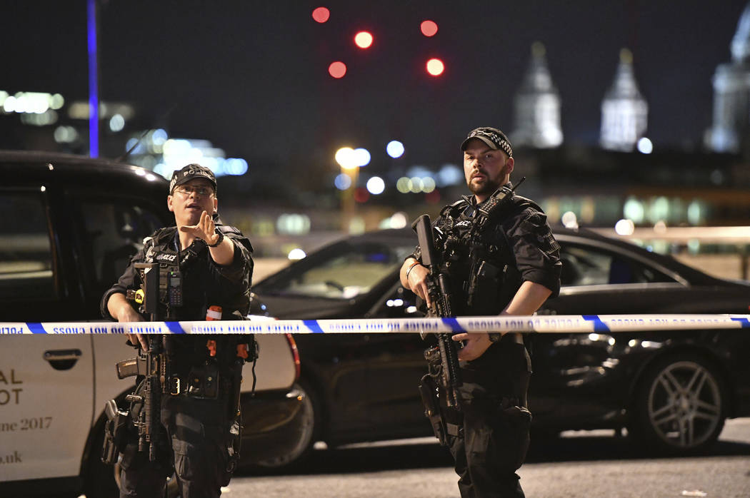 """Armed Police officers stand guard on London Bridge in central London, Saturday, June 3, 2017.  British police said they were dealing with """"incidents"""" on London Bridge and nearby  ..."""