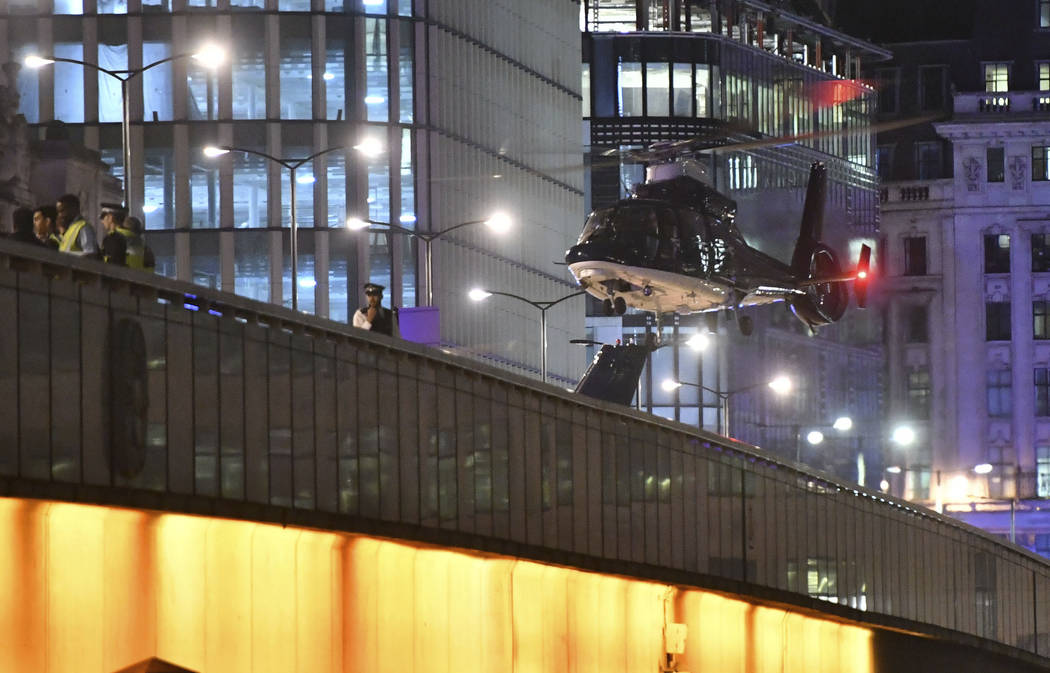 An helicopter lands on London Bridge after an attack in central London, Saturday, June 3, 2017. Armed British police rushed to London Bridge late Saturday after reports of a vehicle running down p ...