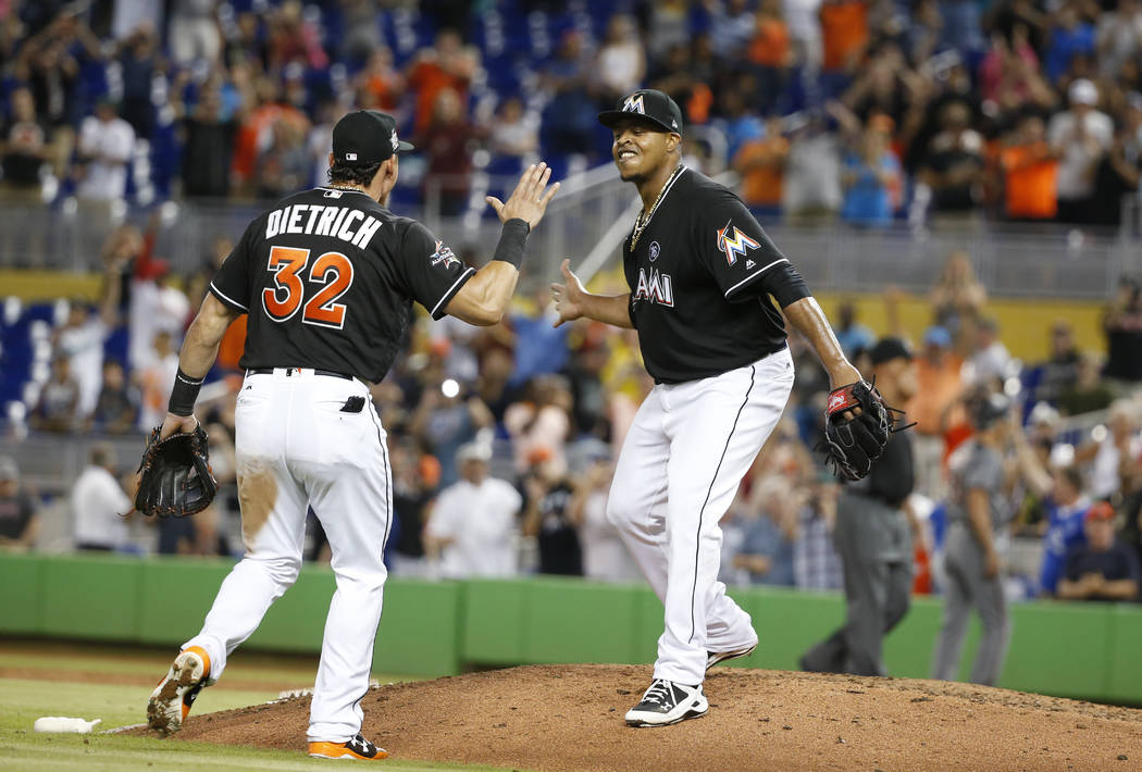 Miami Marlins starting pitcher Edinson Volquez, right, celebrates with Derek Dietrich (32) after throwing a no-hitter as the Marlins defeated the Arizona Diamondbacks 3-0 during a baseball game, S ...
