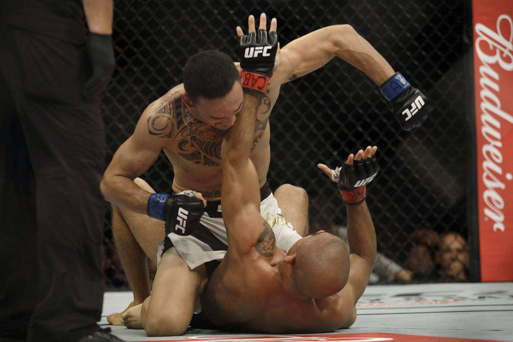 Max Holloway, top, of the United States, fights Jose Aldo, of Brazil, during their UFC featherweight mixed martial arts bout in Rio de Janeiro, Brazil, early Sunday, June 4, 2017. (AP Photo/Leo Co ...