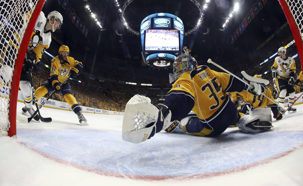Nashville Predators goalie Pekka Rinne (35), of Finland, reaches to make a stop against the Pittsburgh PenguinsGame 3 of the NHL hockey Stanley Cup Final Saturday, June 3, 2017 in Nashville, Tenn. ...