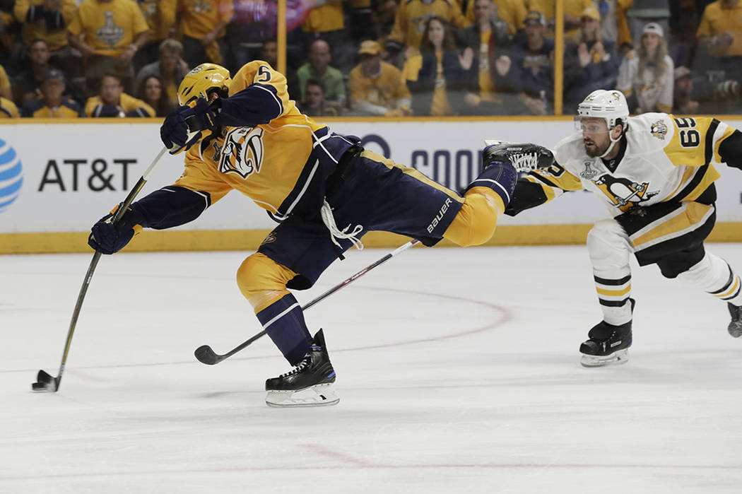 Nashville Predators right wing Craig Smith , left, shoots the puck as Pittsburgh Penguins defenseman Ron Hainsey, right, defends during the third period in Game 3 of the NHL hockey Stanley Cup Fin ...