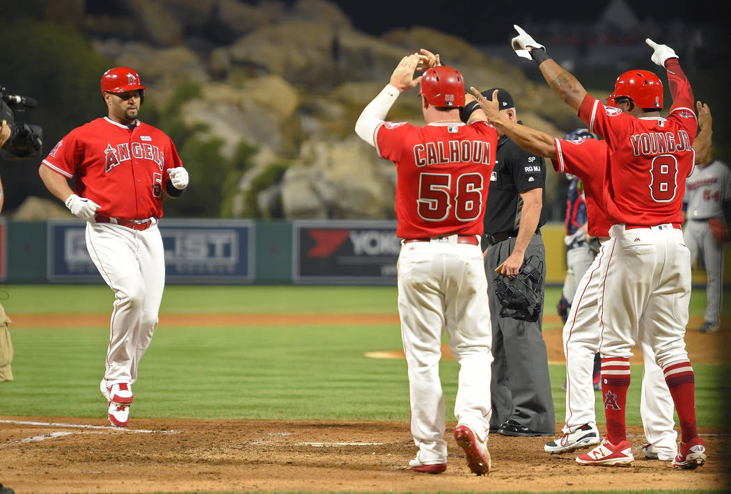 Los Angeles Angels' Albert Pujols, left, scores after hitting a grand slam, the 600th homer of his career, as teammates wait to greet him during the fourth inning of a baseball game against the Mi ...