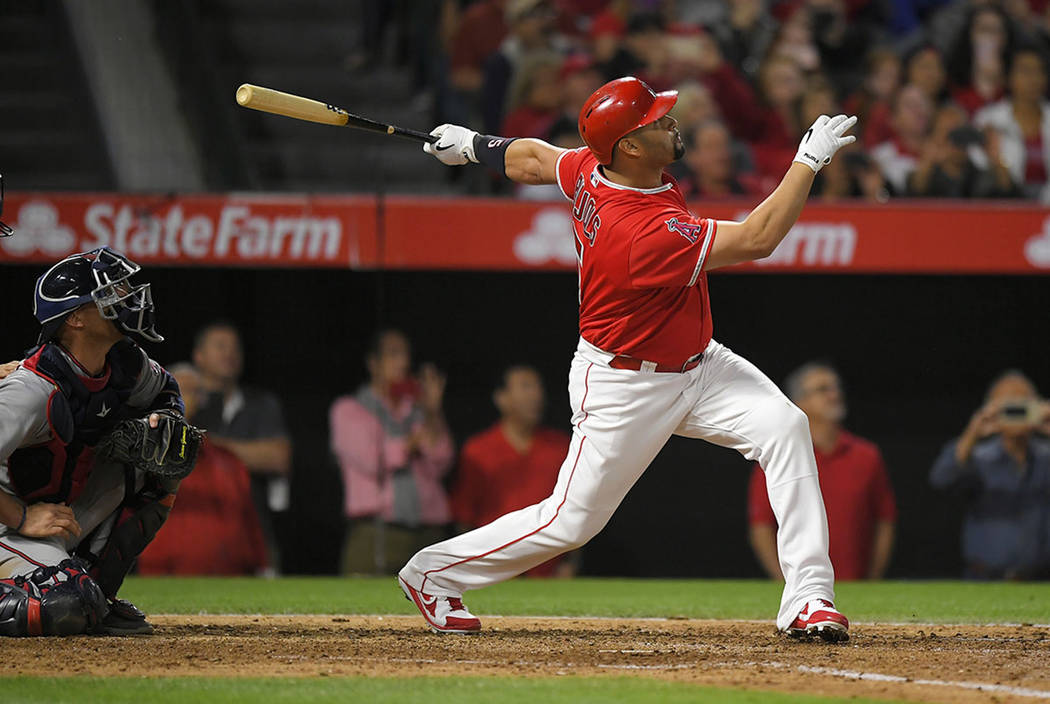 Los Angeles Angels' Albert Pujols, right, follows through on a grand slam, the 600th homer of his career, as Minnesota Twins catcher Chris Gimenez watches during the fourth inning of a baseball ga ...