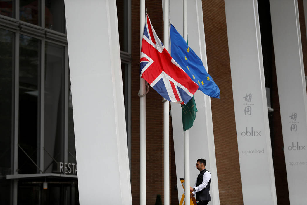 A man lowers the Union and the European Union flags to half mast outside a hotel near the site of an attack left 7 people dead and dozens injured in London, Britain, June 4, 2017. (Peter Nicholls/ ...