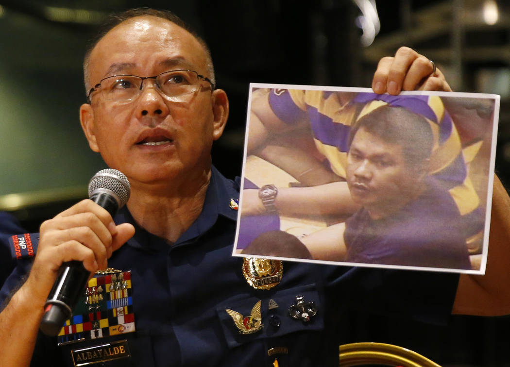 Police Gen. Oscar Albayalde holds a copy of an image of a gunman who stormed the Resorts World Manila complex whom he identified as Jessie Carlos during a news conference Sunday, June 4, 2017 in s ...