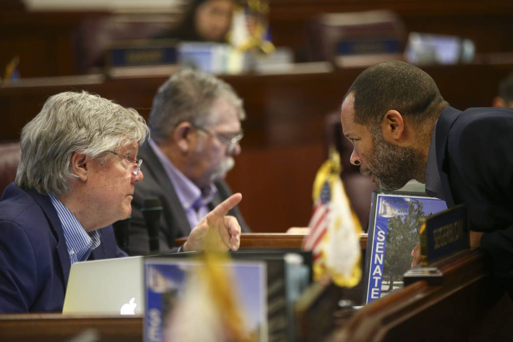 Sen. Tick Segerblom, D-Las Vegas, left, talks with Senate Majority Leader Aaron Ford, D-Las Vegas, during the second to last day of the Nevada Legislature at the Legislative Building in Carson Cit ...