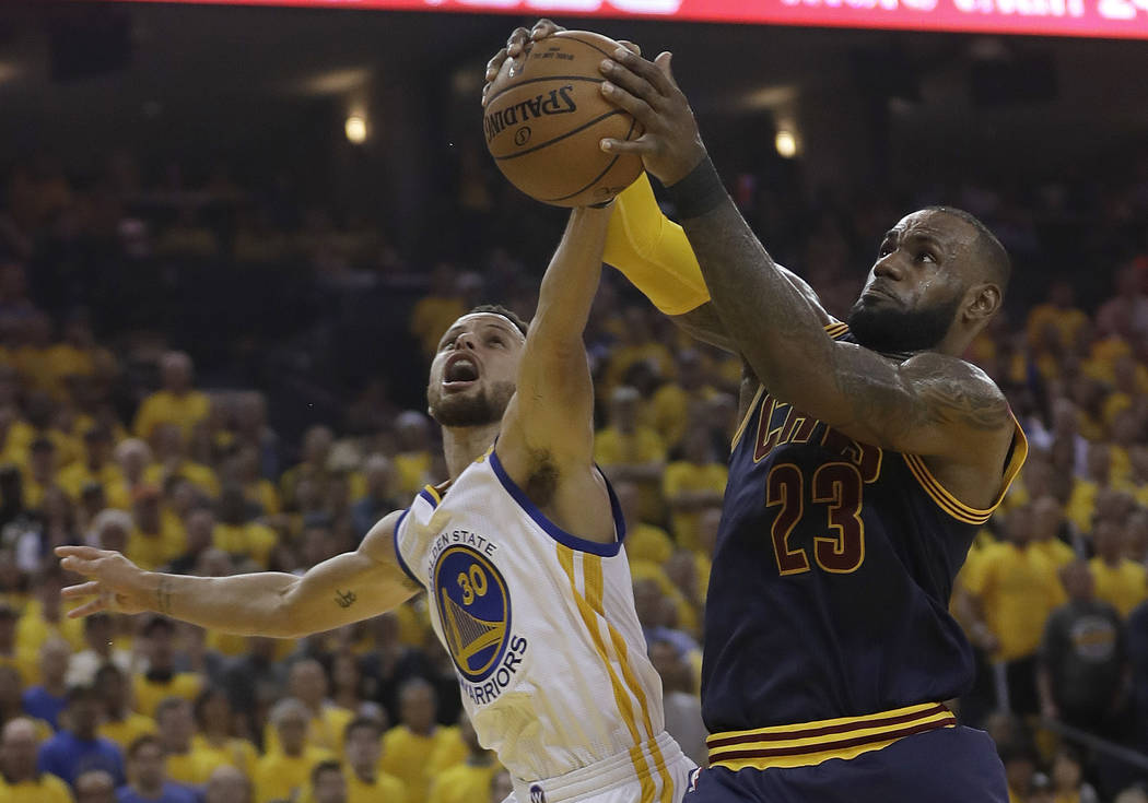 Cleveland Cavaliers forward LeBron James (23) grabs a rebound against Golden State Warriors guard Stephen Curry (30) during the first half of Game 1 of basketball's NBA Finals in Oakland, Calif.,  ...