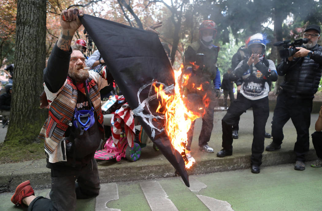 A conservative protester burns an anarchist flag during competing demonstrations in Portland, Oregon, U.S. June 4, 2017. (Jim Urquhart/Reuters)