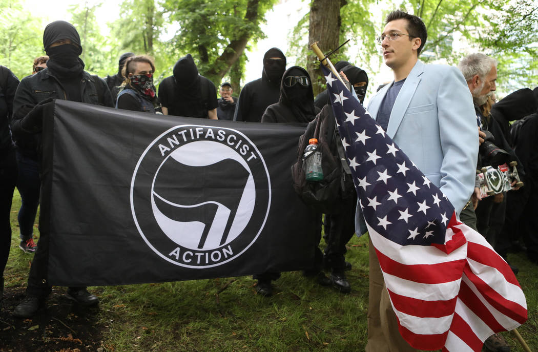 A conservative protester (R) walks past a group of anti-fascist during competing demonstrations in Portland, Oregon, U.S. June 4, 2017. (Jim Urquhart/Reuters)