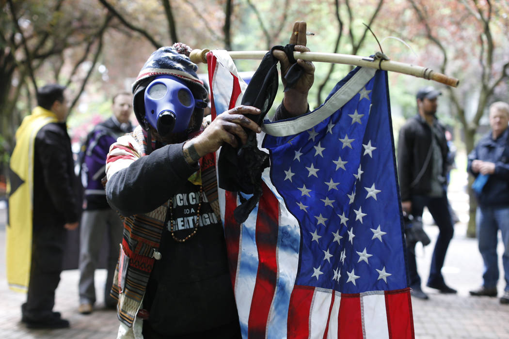 John Durano, who says he flew in from LA to participate and demonstrate his white pride, wears a gas mask and waves an American flag during a demonstration near City Hall and adjacent parks in  Po ...