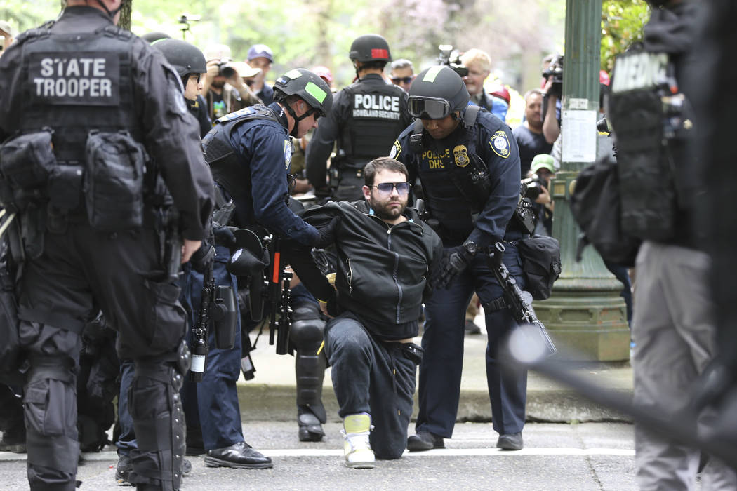 A protester is detained by Portland police during a demonstration in Portland, Sunday, June 4, 2017. Crowds have swelled to several thousand for competing rallies following the fatal stabbing of t ...