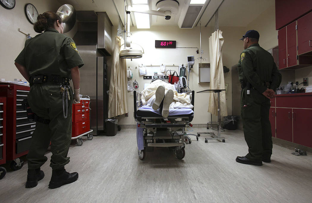Correctional officers stand watch over an inmate receiving treatment in the emergency room at California State Prison, Corcoran, in Corcoran, Calif., in 2009. (AP Photo/Rich Pedroncelli, File)