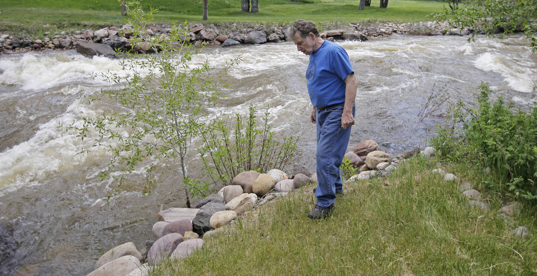Ron Lenfield watches the fast-flowing Weber River along his property, in Oakley, Utah, on May 31. (AP Photo/Rick Bowmer)