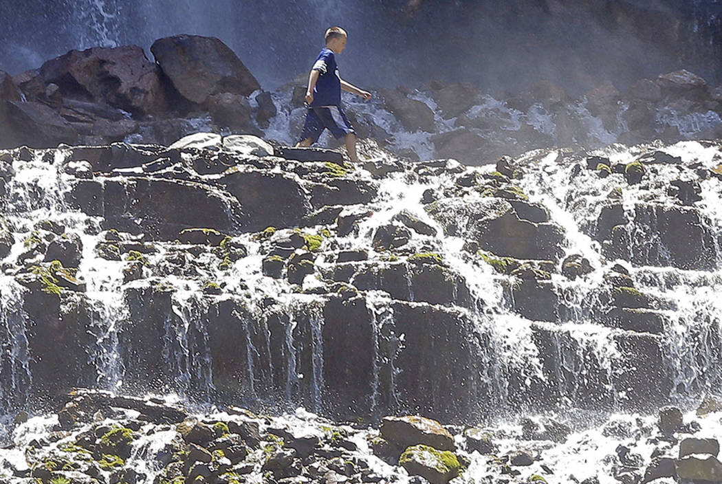 A visitor walks along Bridal Veil Falls along the Provo Canyon, near Provo, Utah, on May 30. (AP Photo/Rick Bowmer)