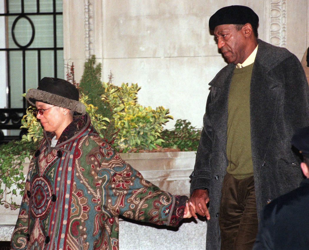 FILE - In this Thursday, Jan. 16, 1997 file photo, Bill Cosby is led from his New York home by his wife, Camille. Cosby's only son, Ennis William Cosby, 27, was shot to death while changing a flat ...