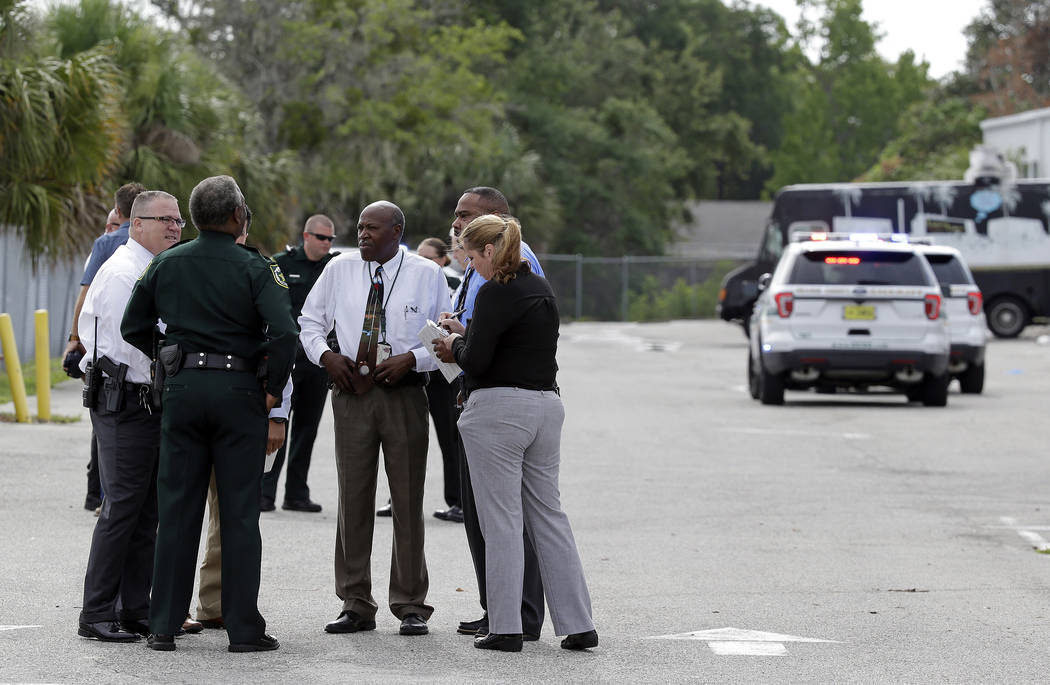 Authorities confer near the scene of a shooting where they said there were multiple fatalities in an industrial area near Orlando, Fla., Monday, June 5, 2017. The Orange County Sheriff's Office sa ...
