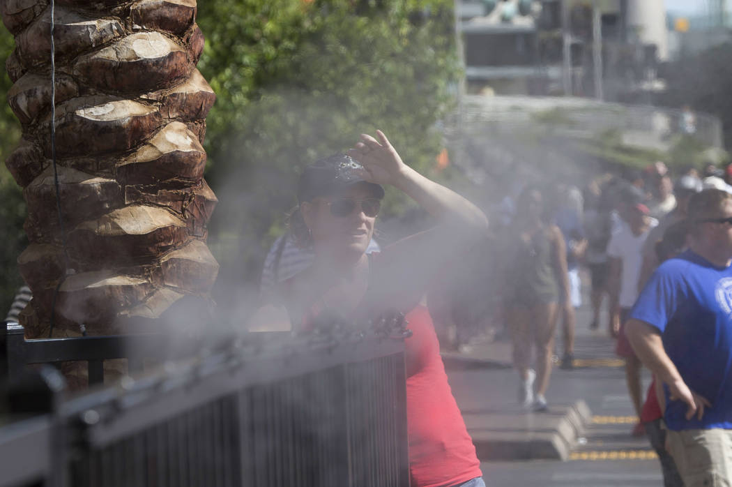 Pedestrians cool off with water misters along the Las Vegas Strip. The highs Monday and Tuesday will reach 104. (Richard Brian Las Vegas Review-Journal) @vegasphotograph