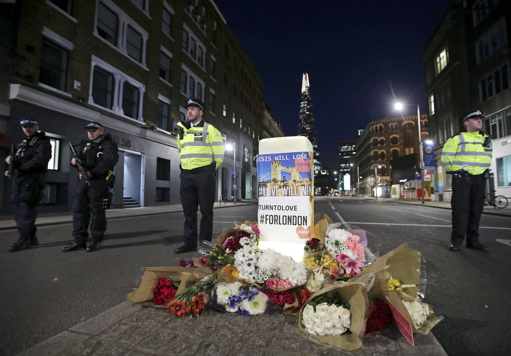 Police officers on duty stand next to floral tributes on Southwark Street in London, Sunday, June 4, 2017, near the scene of Saturday's attack. (Yui Mok/PA via AP)