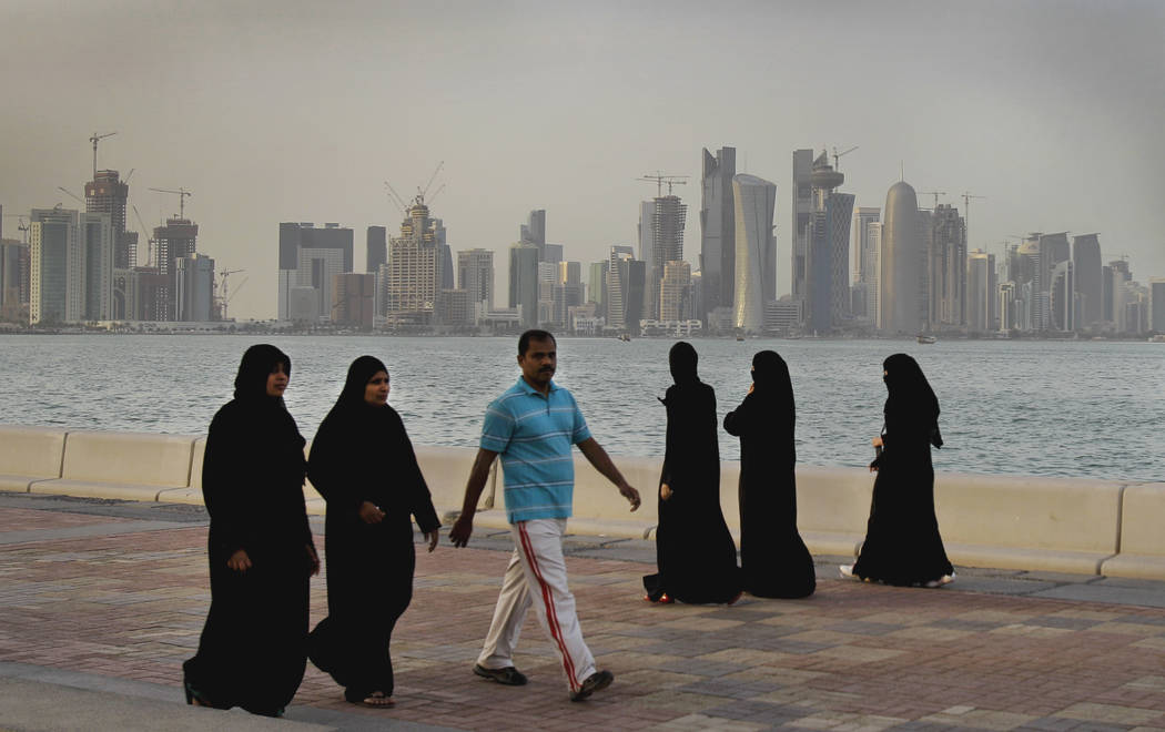 Qatari women and a man walk by the sea in Doha, Qatar, in April 2012 with the new high-rise buildings of downtown Doha in the background. Saudi Arabia and three Arab countries severed ties to Qata ...