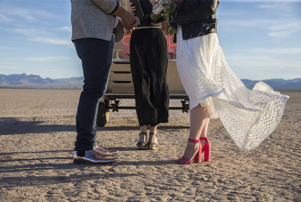 Victoria Hogan, middle, officiates the popup wedding of Joe Brown, left, and Shannon Bray on Tuesday, June 6, 2017, at El Dorado Dry Lake Bed, outside Boulder City. Hogan is the founder of Flora P ...