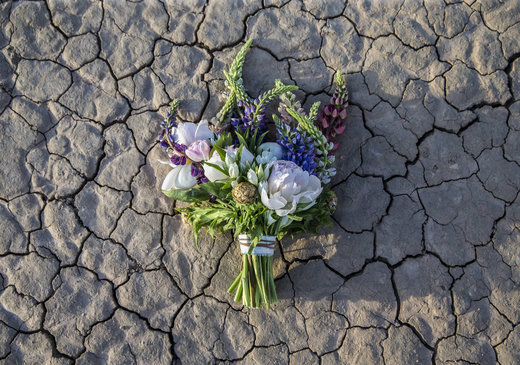 New bride Shannon Bray's bouquet lays on the ground at the conclusion of her popup wedding ceremony  on Tuesday, June 6, 2017, at El Dorado Dry Lake Bed, outside Boulder City. Flora Pop owner Vict ...