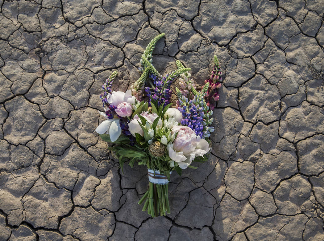 New bride Shannon Bray's bouquet lays on the ground at the conclusion of her popup wedding ceremony on Tuesday, June 6, 2017, at El Dorado Dry Lake Bed, outside Boulder City. Flora Pop owner Victo ...