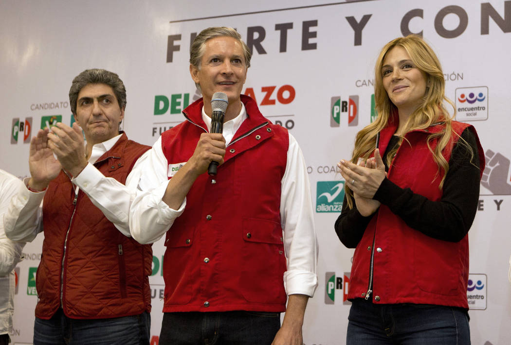 Alfredo Del Mazo, gubernatorial candidate for the ruling Institutional Revolutionary Party, or PRI, stands with his wife Fernanda Castillo, right, and members of his team as he addresses the press ...