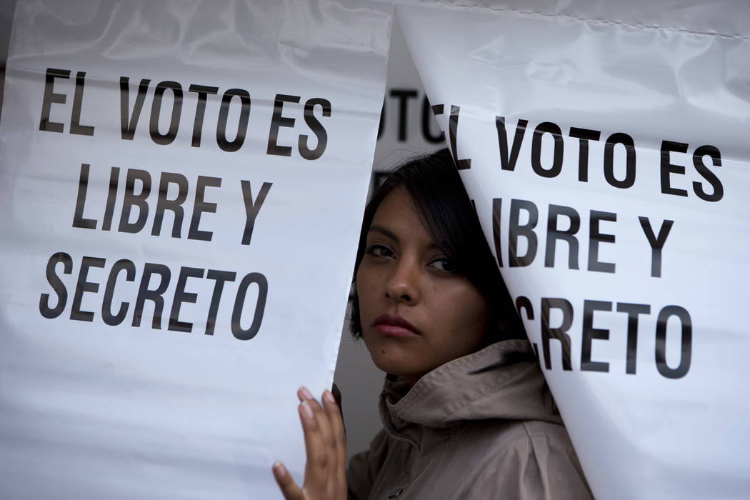 "A woman emerges from a privacy booth, reading in Spanish ""The vote is free and secret,"" after marking her ballot for governor at a polling station in Chimalhuacan, Mexico state,  ..."