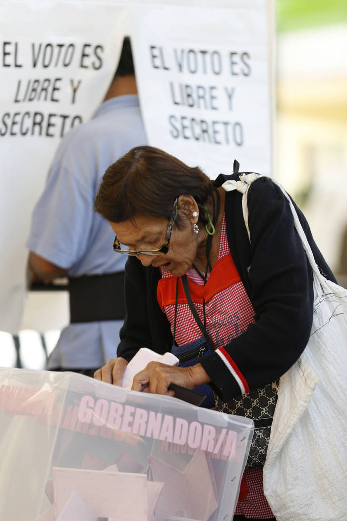 A woman casts her vote for Mexico State governor at a polling station in Ecatepec, Mexico, Sunday, June 4, 2017. Voters in Mexico's most populous state on Sunday could hand the ruling PRI party a  ...