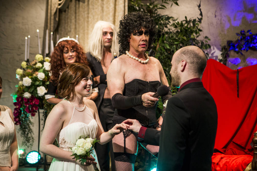 Ron Decar, owner of Viva Las Vegas and dressed as Frank-N-Furter from the Rocky Horror Picture Show, has Alex Spivak recite his vows while wedding Dominique Lehn at the Viva Las Vegas Wedding Chap ...