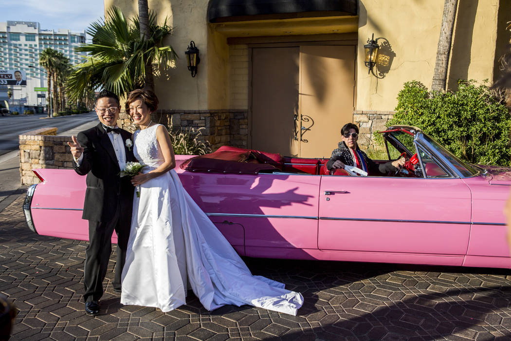 Garry and Julie Kim take photos next to the pink Cadillac after renewing their wedding vows in an Elvis-themed ceremony at the Viva Las Vegas Wedding Chapel on Saturday, June 3, 2017.  Patrick Con ...
