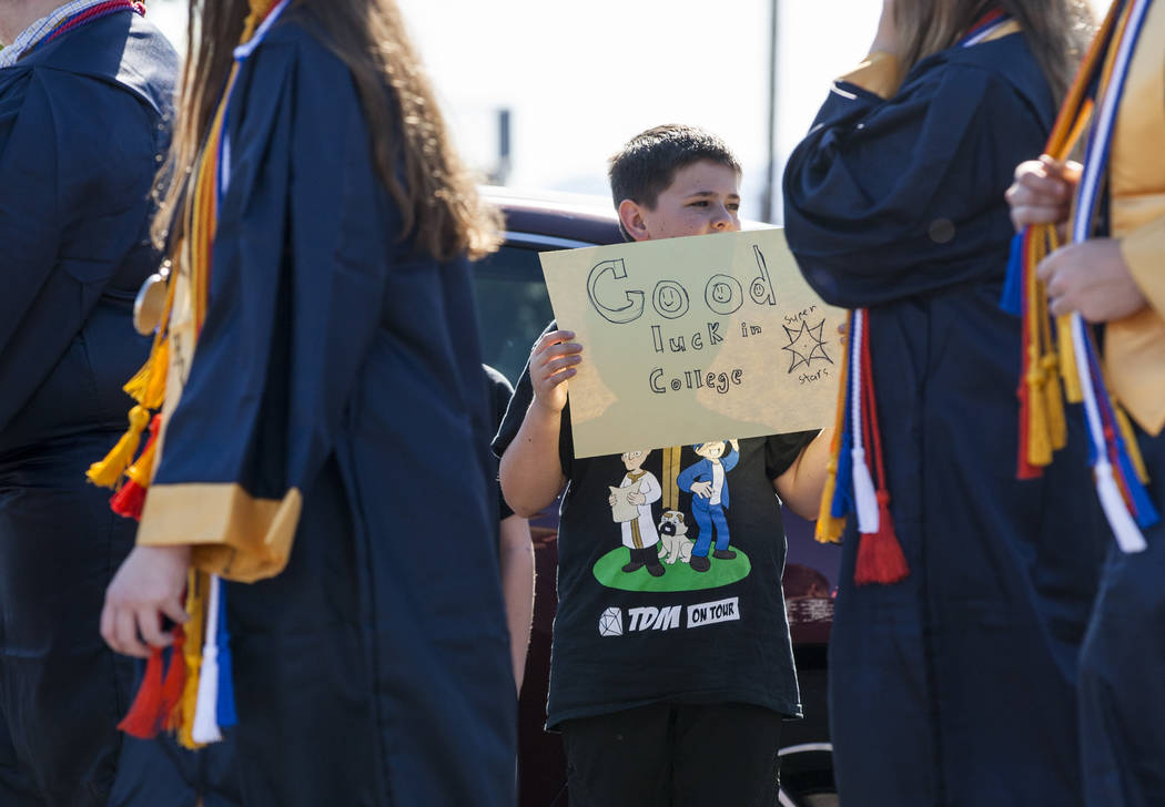 An elementary schooler holds up a sign for Boulder City High School seniors as they walk in an annual Grad Walk to celebrate the their accomplishments and encourage young students to finish high s ...