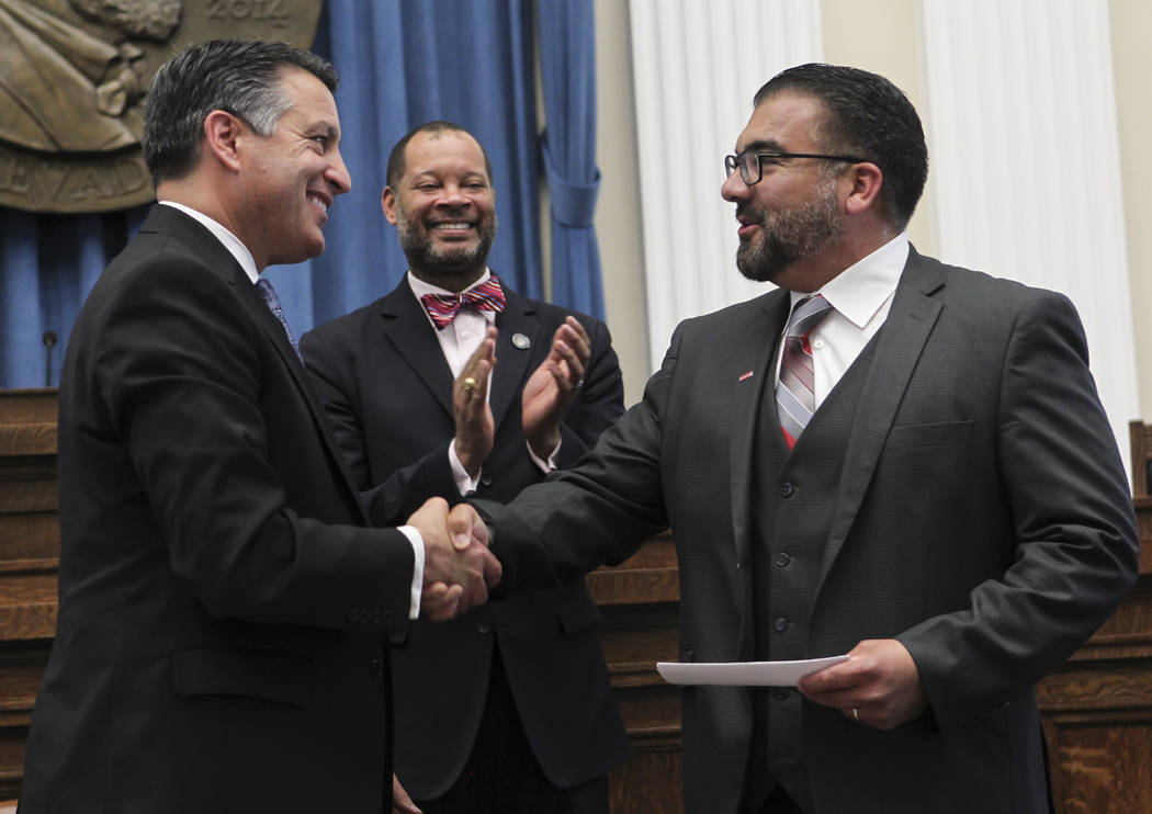 Gov. Brian Sandoval, left, after presenting a $25,000,000 check from an anonymous donor for the UNLV medical school to Luis Valera, vice president for government affairs and compliance at UNLV, ri ...