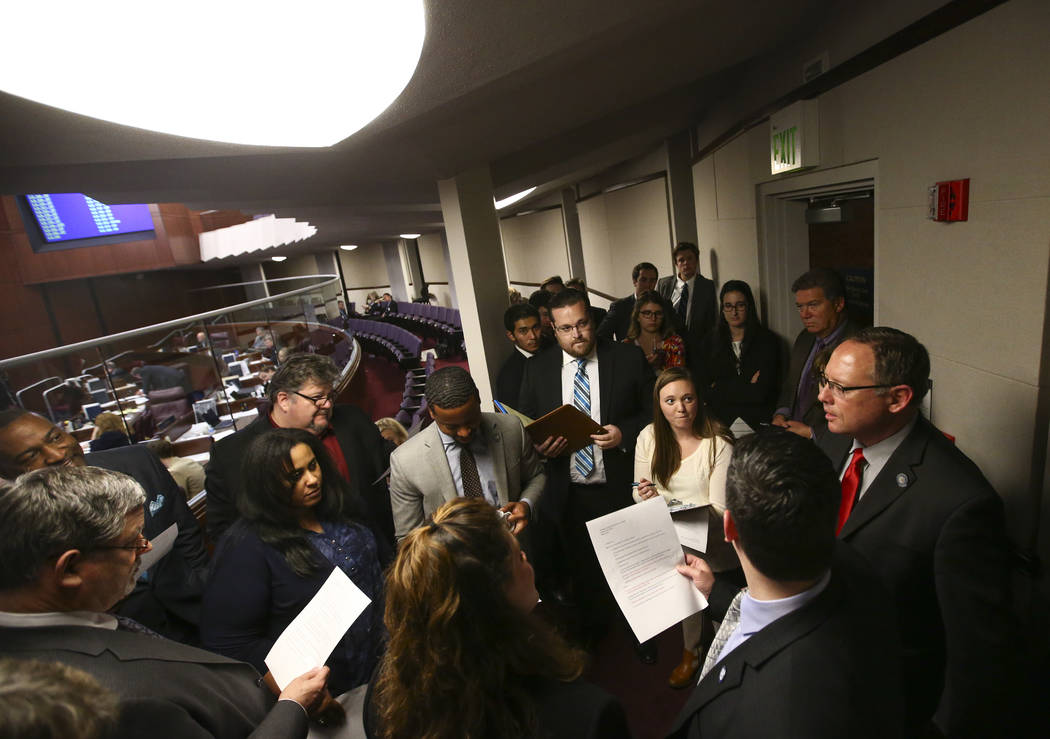 "Members of the Assembly Committee on Health and Human Services meet ""behind the bar"" in the Assembly Chambers at the Legislative Building in Carson City during the early hours of ..."