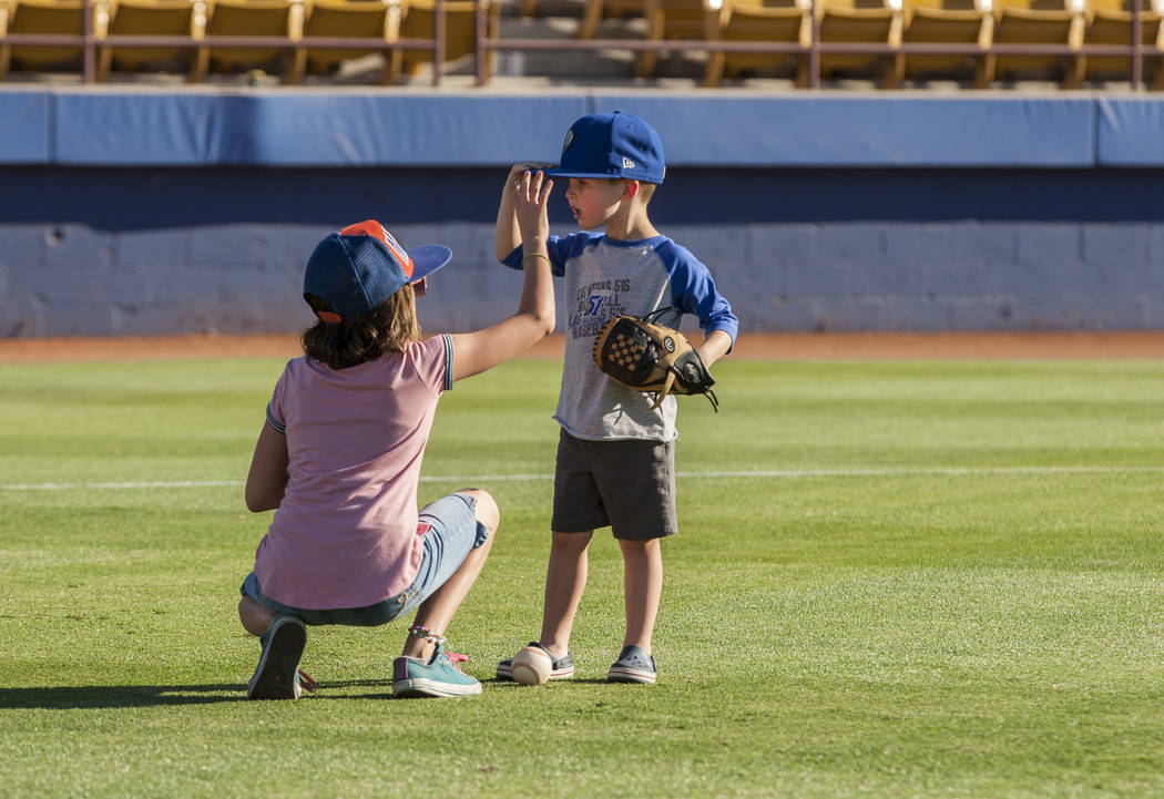 Madison Truman, 9, helps her brother Dillon, 4, adjust his hat during father and child catch, an annual tradition, before the Las Vegas 51s game at Cashman Field on Friday, June 16, 2017.  Patrick ...