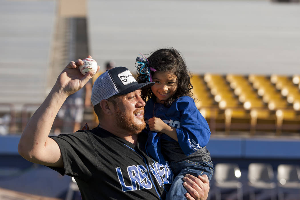 Leo Orozco holds his friend's daughter, Ashley Porter, 5, while throwing the ball during father and child catch, an annual tradition, before the Las Vegas 51s game at Cashman Field on Friday, June ...