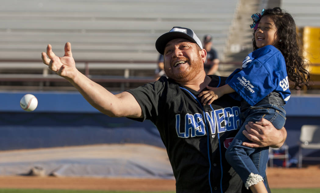 Leo Orozco holds his friend's daughter, Ashley Porter, 5, while attempting to catch the ball during father and child catch, an annual tradition, before the Las Vegas 51s game at Cashman Field on F ...
