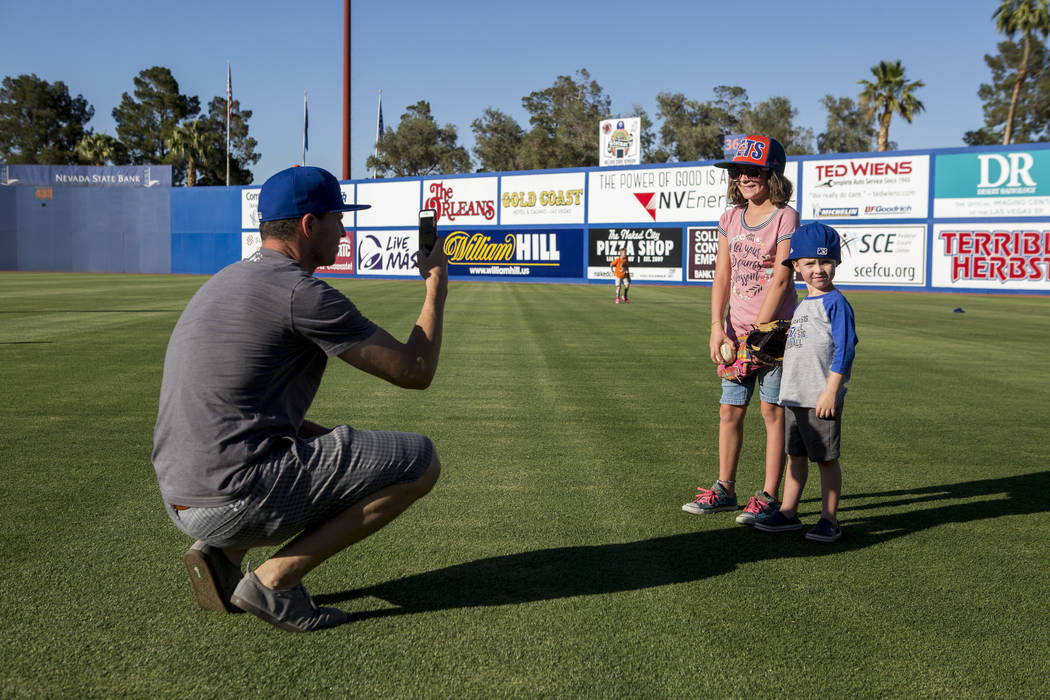 Jared Truman takes a photo of his children Madison, 9, and Dillon, 4, during father and child catch, an annual tradition, before the Las Vegas 51s game at Cashman Field on Friday, June 16, 2017.   ...