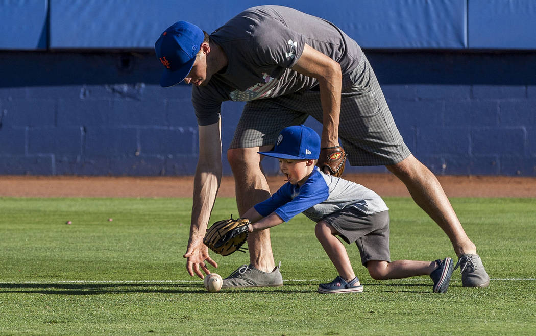 Dillon Truman, 4, races for the ball with his father Jared during father and child catch, an annual tradition, before the Las Vegas 51s game at Cashman Field on Friday, June 16, 2017.  Patrick Con ...