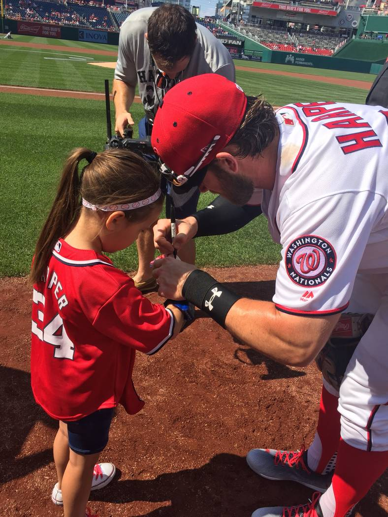 Las Vegas' Bryce Harper signs the baseball for fellow Las Vegan Hailey Dawson after she threw out the ceremonial first pitch before the June 11 game between the Washington Nationals and Texas Rang ...